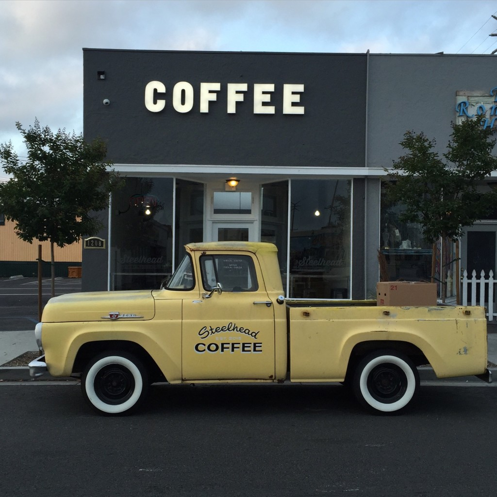 a yellow vintage ford f150 is shown parked in front of steelhead coffee shop. steelhead coffee is printed on the door of the truck. the word coffee is used as the store sign.